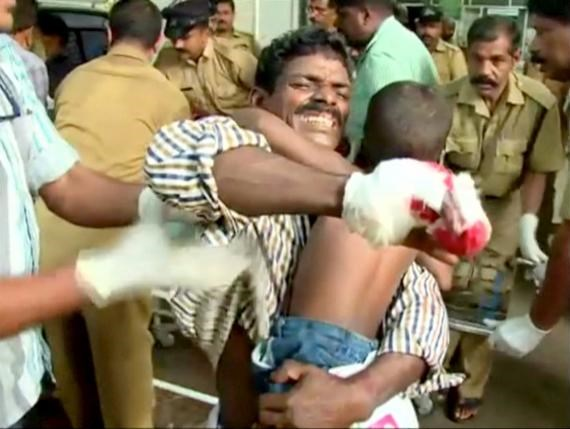 An injured man carries his child before receiving medical attention at a hospital, after a fire broke out as people gathered for a fireworks display at a temple in Kollam, southern India, in this still image taken from video April 10, 2016. Photo: Reuters/ANI via REUTERS TV