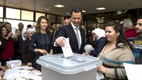 Syria's President Bashar al-Assad (C) casts his vote next to his wife Asma (centre left) inside a polling station during parliamentary elections in Damascus, Syria, in this handout picture provided by SANA on April 13, 2016. Photo: Reuters/SANA/Handout via Reuters