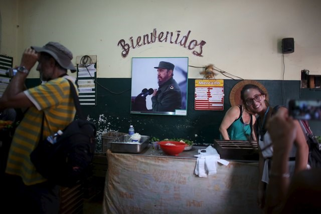 "Tourists take pictures inside a state run market where a picture of Cuba's former president Fidel Castro is seen on the wall which reads ""Welcome"", Havana, March 28, 2016. Photo: Reuters/Alexandre Meneghini"
