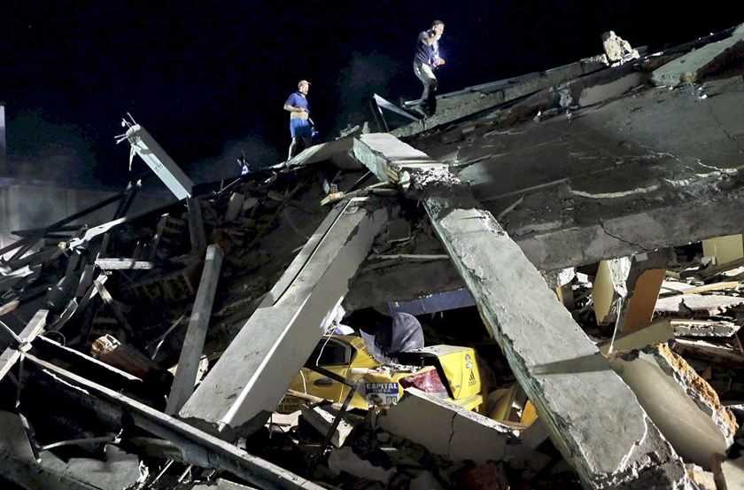 Workers walk on top of the debris of a collapsed hotel under which a flattened taxi is seen after an earthquake struck off the Pacific coast, in Portoviejo, Ecuador, April 17, 2016. Photo: Reuters/Henry Romero