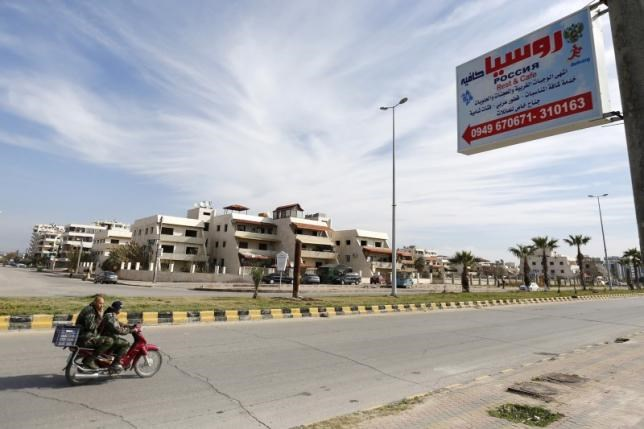 Syrian pro-government forces ride a motorcycle past a road sign of a restaurant named 'Russia' in the Mediterranean coastal city of Latakia, Syria January 28, 2016.Photo: Reuters/Omar Sanadiki