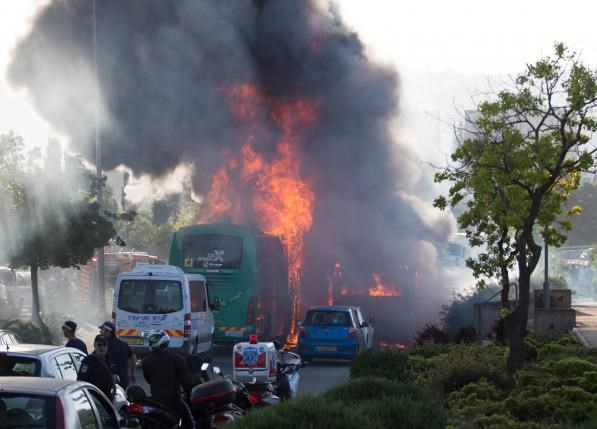 Flames rise at the scene where an explosion tore through a bus in Jerusalem on Monday setting a second bus on fire, in what an Israeli official said was a bombing, April 18, 2016. Photo: Reuters/Noam Revkin Fenton