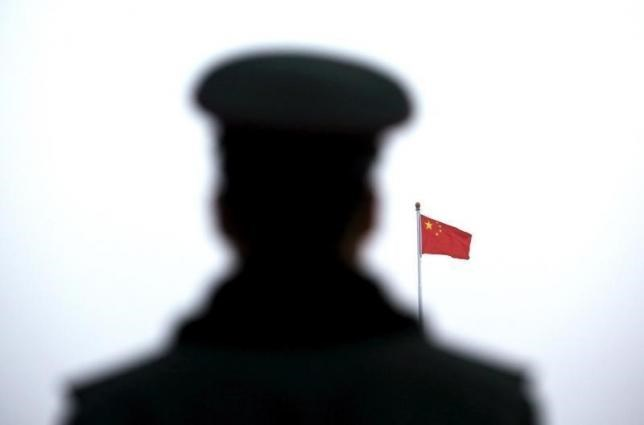 A paramilitary policeman watches a flag-raising ceremony at Tiananmen Square ahead of the opening session of the National People's Congress (NPC) in Beijing, China, March 5, 2016. Photo: Reuters/Kim Kyung-Hoon