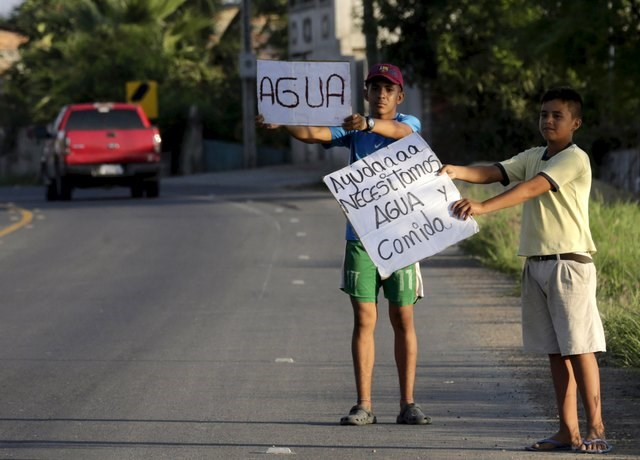 "Local residents hold up posters along a road near the village of Manta, after an earthquake struck off Ecuador's Pacific coast, April 20, 2016. The words read : ""We need food and water"". Photo: Reuters/Henry Romero"