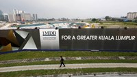 A man walks past a 1 Malaysia Development Berhad (1MDB) billboard at the funds flagship Tun Razak Exchange development in Kuala Lumpur, in this March 1, 2015 file photo. Photo: Reuters/Olivia Harris