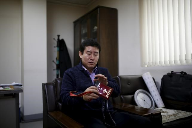 Seo Jae-pyoung, the secretary general of the association of the North Korean defectors, looks at a Workers' Party membership card holder while demonstrating the use of it during an interview with Reuters in Seoul, South Korea, April 22, 2016. Photo: Reuters/Kim Hong-Ji
