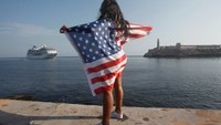 A woman with a U.S. flags looks at the arrival of U.S. Carnival cruise ship Adonia at the Havana bay, the first cruise liner to sail between the United States and Cuba since Cuba's 1959 revolution, Cuba, May 2, 2016. Photo: Reuters/Stringer