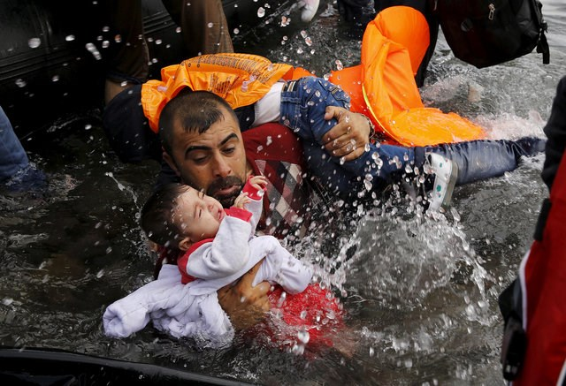 A Syrian refugee holds onto his children as he struggles to walk off a dinghy on the Greek island of Lesbos, after crossing a part of the Aegean Sea from Turkey to Lesbos September 24, 2015. Photo: Reuters/Yannis Behrakis/File photo