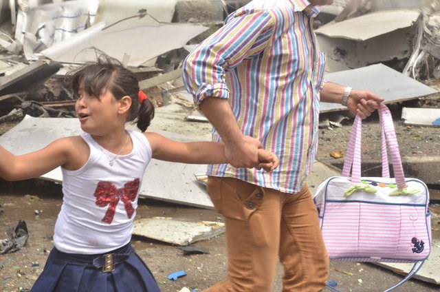 A man holds the hand of a girl as they rush out after rebels bombarded government-held areas of Aleppo, Syria, in this handout picture provided by SANA on May 3, 2016. Photo: SANA/Handout via REUTERS