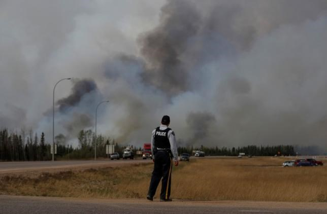 An RCMP police officer looks over the wildfires near Fort McMurray, Alberta, Canada, May 7, 2016. Photo: Reuters/Mark Blinch