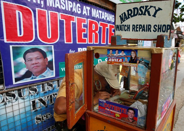 "A watch maker and a supporter of leading presidential candidate Rodrigo ""Digong"" Duterte works on his sidewalk shop in front of a Duterte election campaign poster in Davao city in southern Philippines, May 10, 2016. Photo: Reuters/Erik De Castro"