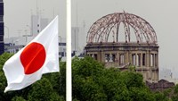 The Japanese national flag flutters at half-mast in the foreground of the atomic bomb dome at the Hiroshima Peace Memorial Park, in western Japan August 6, 1998. Photo: Reuters/Kimimasa Mayama/File Photo