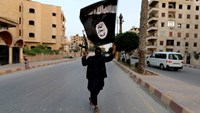 A member loyal to Islamic State waves a flag in Raqqa June 29, 2014. Photo: Reuters/Stringer