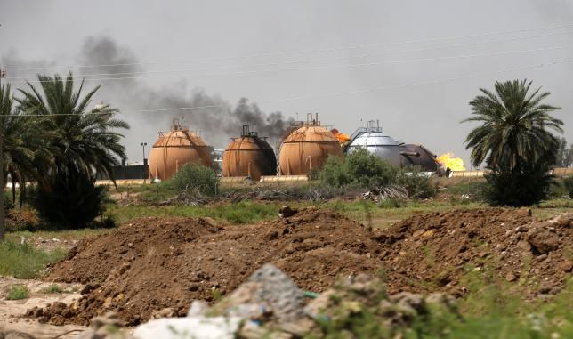 Smoke rises from gas storage tanks after a bomb attack against a state-run cooking gas factory in Taji at Baghdad's northern outskirts, Iraq May 15, 2016. Photo: Reuters/Thaier Al-Sudani
