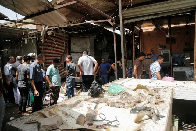 People gather at the site of a suicide bomb attack in a marketplace in Baghdad's al-Shaab district, Iraq May 17, 2016. Photo: Reuters/Wissm al-Okili