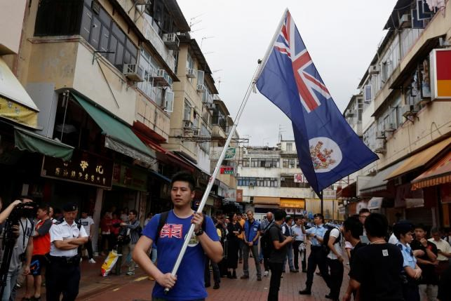 A local man carries a British Hong Kong colonial flag in Hong Kong, China, May 1, 2016. Photo: Reuters/Bobby Yip