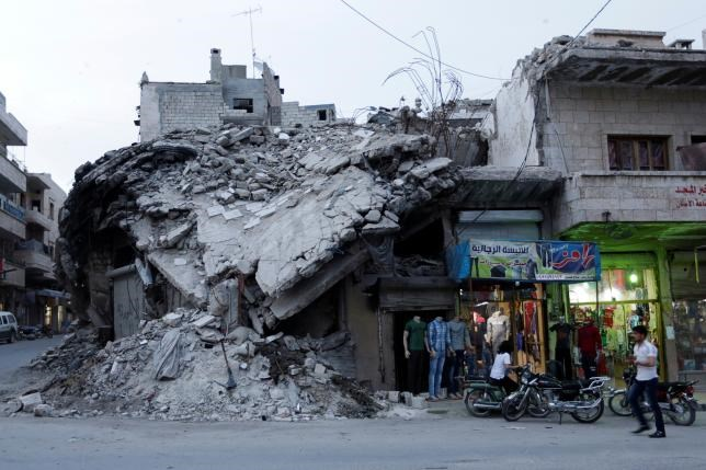 A clothing shop displays its merchandise beside a damaged building in the rebel-controlled area of Maaret al-Numan town in Idlib province, Syria, May 15, 2016. Photo: Reuters/Khalil Ashawi