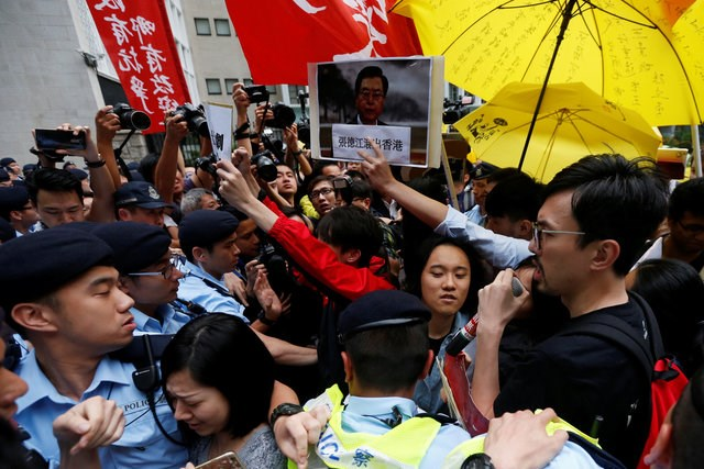 Police officers block protesters holding a portrait of Zhang during a demonstration against a visit by Zhang Dejiang, the chairman of China's National People's Congress, in Hong Kong May 17, 2016. Photo: Reuters/Bobby Yip