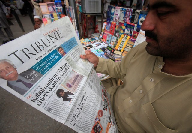 A man reads a newspaper containing news about Afghan Taliban leader Mullah Akhtar Mansour at a stall in Peshawar, Pakistan, May 23, 2016. Photo: Reuters/Fayaz Aziz