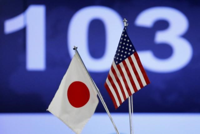Japanese (L) and American flags are displayed in front of a monitor showing the Japanese yen's exchange rate against the U.S. dollar, in Tokyo December 3, 2013. Photo: Reuters/Issei Kato