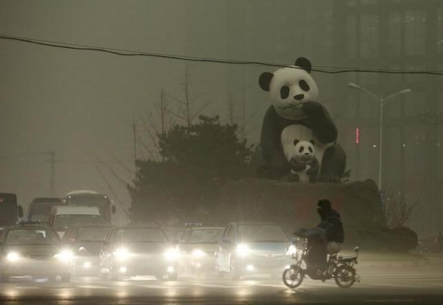A resident rides an electric bicycle across a street amid heavy smog as vehicles wait for a traffic light next to a statue of pandas, a landmark of the Wangjing area in Beijing, China, December 1, 2015. Photo: Reuters/China Daily