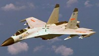 File photo of a Chinese J-11 fighter jet seen flying near a U.S. Navy P-8 Poseidon about 215 km (135 miles) east of China's Hainan Island in this U.S. Department of Defense handout photo taken August 19, 2014. Photo: Reuters/U.S. Navy/Handout
