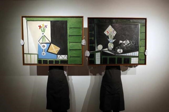 Art handlers pose with 'Nature morte' (L) and 'Nature morte aux volets verts' by Pablo Picasso, at Christie's auction house in London, Britain, June 1, 2016. Photo: Reuters/Stefan Wermuth