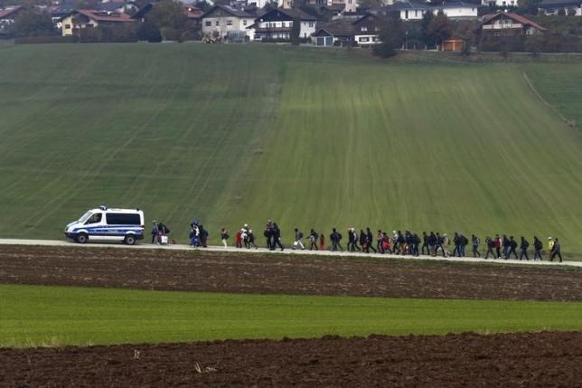 Immigrants are escorted by German police to a registration centre, after crossing the Austrian-German border in Wegscheid near Passau, Germany, October 20, 2015. Photo: Reuters/Michael Dalder