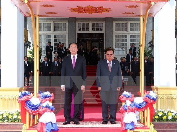 Vietnam's President Tran Dai Quang (L) and Lao Party General Secretary and President Bounnhang Vorachith at an official welcome ceremony in Vientiane On June 12, 2016. Photo: VNA