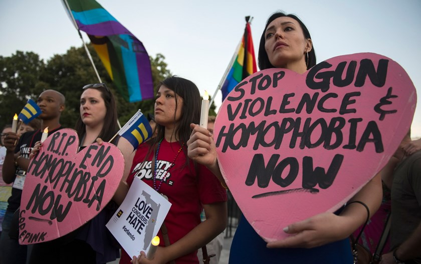 Mourners hold up signs during a vigil in Washington, DC on June 12, 2016, in reaction to the mass shooting at a gay nightclub in Orlando, Florida. Fifty people died when a gunman allegedly inspired by the Islamic State group opened fire inside a gay nightclub in Florida, in the worst terror attack on US soil since September 11, 2001. Photo: AFP/Andrew Caballero-Reynolds