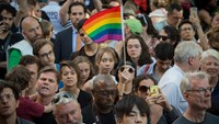 People wave flags during a vigil in reaction to the mass shooting at a gay nightclub in Orlando, Florida,in New York on June 12, 2016. Photo: AFP / Bryan R. Smith