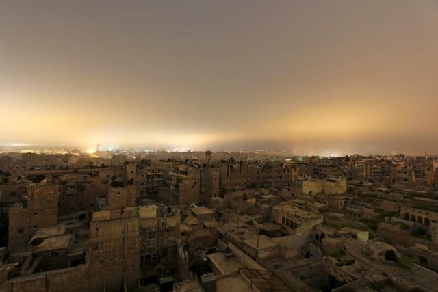A general view shows damaged buildings in Aleppo city at night April 11, 2015. Photo: Reuters/Rami Zayat
