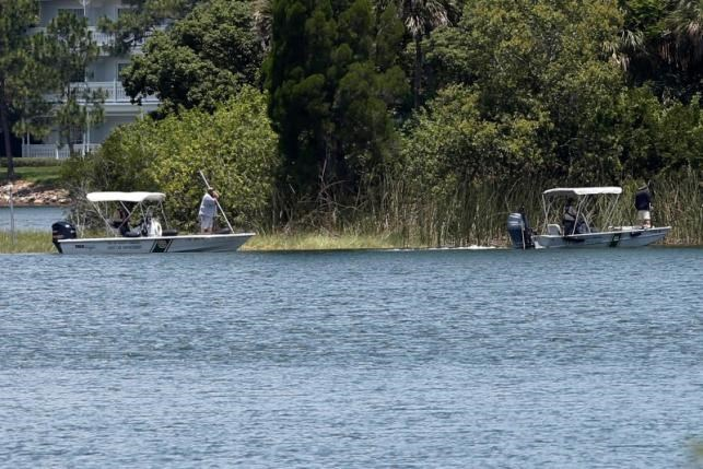 Wildlife officials search the Seven Seas lagoon at Walt Disney World resort after an alligator dragged a two-year-old boy into the water in Orlando, Florida, June 15, 2016. Photo: Reuters/Adrees Latif