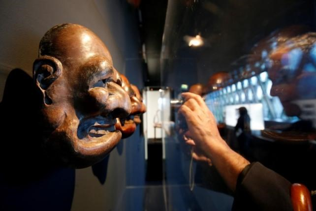 A visitor takes a picture of a Bugaku Japanese mask (18eme) from traditional Kyogen comic theatre that is displayed during the exhibition 'Jacques Chirac ou le dialogue des cultures' at the Musee du quai Branly in Paris, France, June 20, 2016. Photo: Reuters/Jacky Naegelen
