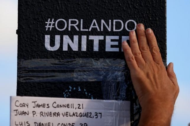 A person rubs an '#Orlando United' sticker on the sign pole outside Pulse nightclub following the mass shooting last week in Orlando, Florida, U.S., June 21, 2016. Photo: Reuters/Carlo Allegri