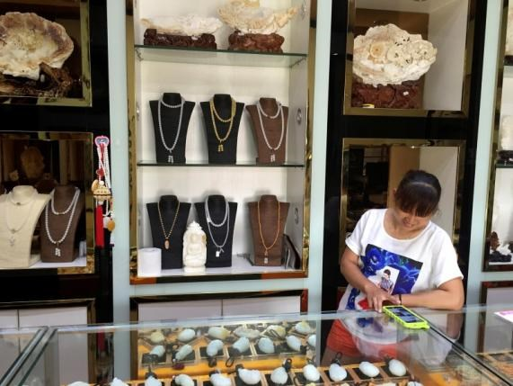 Products made from giant clam shells are displayed inside a store in the seaside town of Tanmen in China's Hainan province May 10, 2016. Photo: Reuters/Farah Master