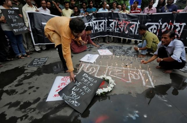 A man places a sign as others light candles during a vigil in Kolkata, India, to show solidarity with the victims of the attack at Holey Artisan restaurant after Islamist militants attacked the upscale cafe in Dhaka, Bangladesh, July 2, 2016. Photo: Reuters/Rupak De Chowdhuri