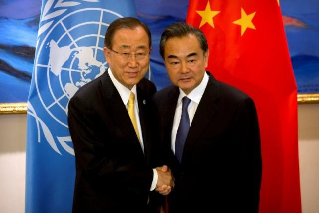 U.N. Secretary General Ban Ki-moon, left, shakes hands with Chinese Foreign Minister Wang Yi, right, at the Diaoyutai State Guesthouse in Beijing, Thursday, July 7, 2016. Photo: Reuters/Mark Schiefelbein/Poo