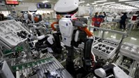 Humanoid robots work side by side with employees in the assembly line at a factory of Glory Ltd., a manufacturer of automatic change dispensers, in Kazo, north of Tokyo, Japan, July 1, 2015. Photo: Reuters/Issei Kato