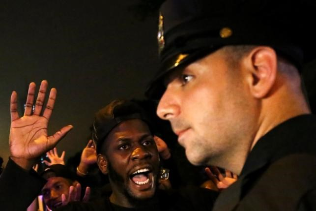 A protester shouts 'Look at me' towards a NYPD police officer during a march against police brutality in Manhattan, New York, U.S., July 9, 2016. Photo: Reuters/Bria Webb