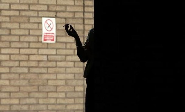 A woman smokes in the shadows outside Southwark Crown Court in central London, March 5, 2014. Photo: Reuters/Andrew Winning