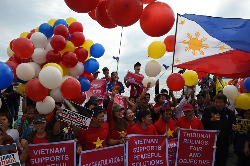 Filipino activists and Vietnamese nationals release balloons and wave Philippine flags as they anticipate a favorable decision from a UN tribunal ruling on the legality of China's claims to an area of the South China sea contested by the Philippines, during a demonstration along the bay walk in Roxas Boulevard in Manila on July 12, 2016. Photo: AFP / TED ALJIBE