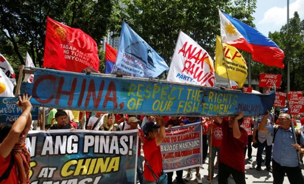 Demonstrators display a part of a fishing boat with anti-China protest signs during a rally by different activist groups over the South China Sea disputes, outside the Chinese Consulate in Makati City, Metro Manila, Philippines July 12, 2016. Photo: Reuters/Erik De Castrby