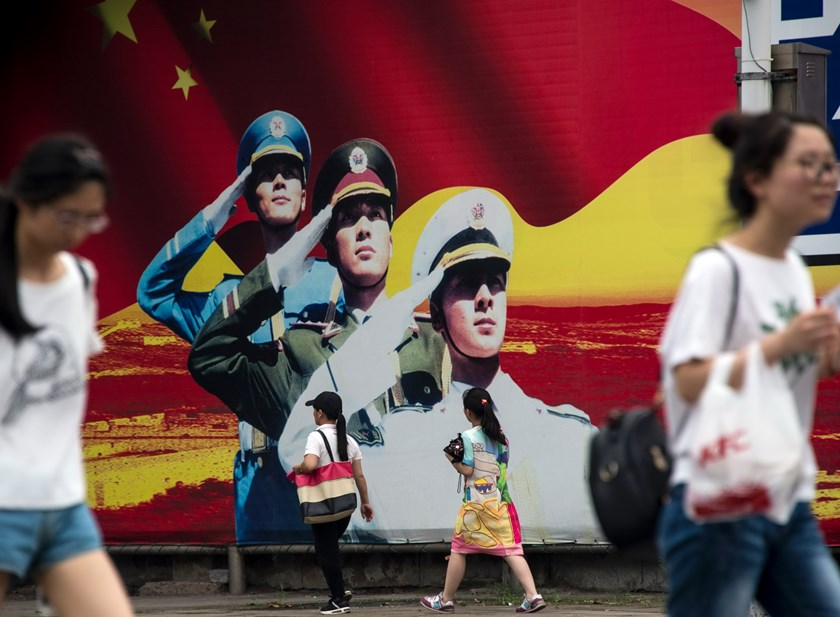 Pedestrians pass a military propaganda poster on a street in Shanghai on July 12, 2016. Photo: AFP / JOHANNES EISELE