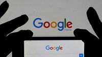 A woman holds her smart phone which displays the Google home page, in this picture illustration taken February 24, 2016. Photo: Reuters/Eric Gaillard/Illustration/Files