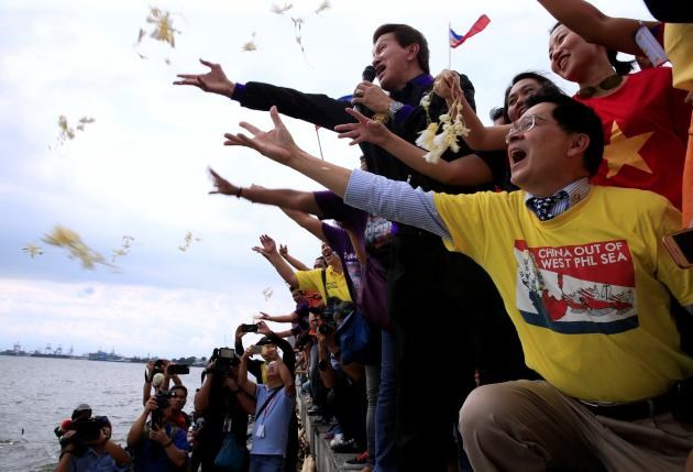 Protesters throws flowers while chanting anti-Chinese slogans during a rally by different activist groups over the South China Sea disputes, along a bay in metro Manila, Philippines July 12, 2016. Reuters/Romeo Ranoco