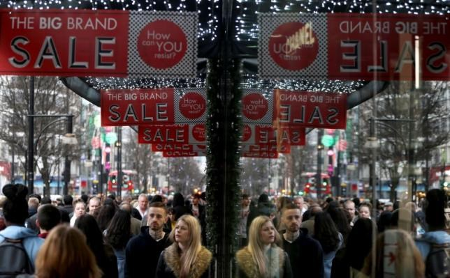 Shoppers are reflected in a store window as they pass sales advertisements on Oxford Street in London, Britain, December 26, 2015. Photo: Reuters/Neil Hall/File Photo