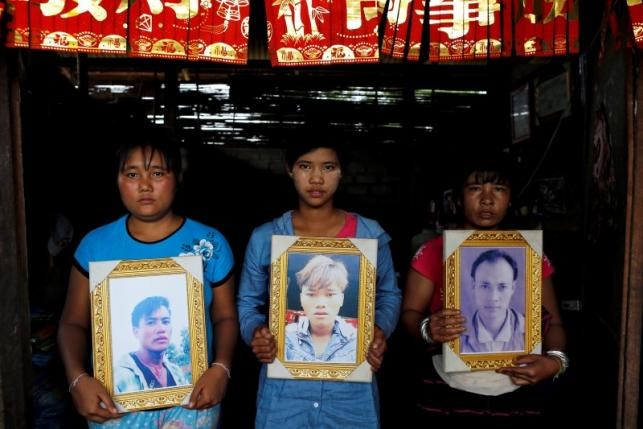 Women pose while holding portraits of their killed relatives (L-R) Aik Sai, Aik Maung and Aik Lort after their bodies were found in a grave last June at Mong Yaw village in Lashio, Myanmar July 10, 2016. Photo: Reuters/Soe Zeya Tun
