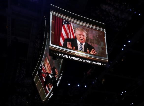 U.S. Republican Presidential Nominee Donald Trump is shown on video monitors as he speaks live to the crowd from New York at the Republican National Convention in Cleveland, Ohio, U.S. July 19, 2016.Photo: Reuters/Mario Anzuoni