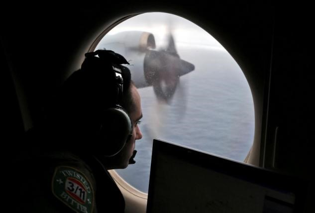 Flight officer Rayan Gharazeddine looks out of a Royal Australian Air Force (RAAF) AP-3C Orion as it flies over the southern Indian Ocean during the search for missing Malaysian Airlines flight MH370 March 22, 2014. Photo: Reuters/Rob Griffith/Pool/File Photo